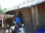 Alexander (ACT) explaining to a family the importance of the nets, how to use them, and how to maintain them.